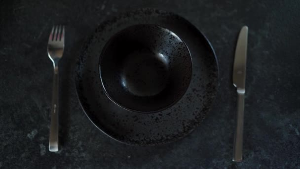 Ženský ruce dávají dvě barevný velikonoční vajíčka do prázdnýho černýho talíře na tmavým pozadí. Zavřít