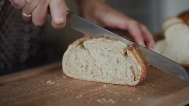 Woman or cook cutting fresh bread in kitchen, close up