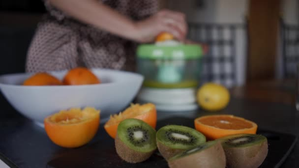 Ripe sliced kiwi and oranges are on a black table. Making freshly squeezed juice in the background is blurry. Close up