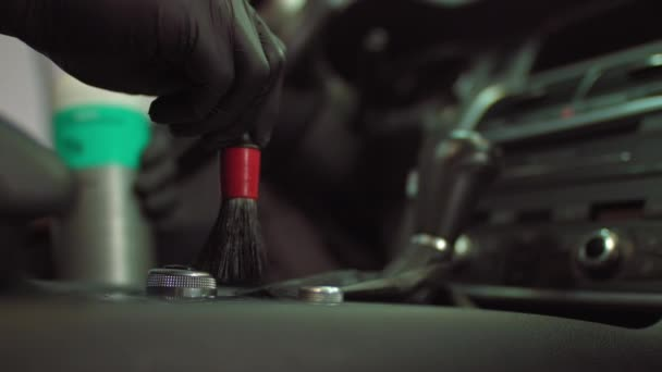 Mytí aut, muž čistí řadící páku štětcem, čistí části od prachu a špíny
