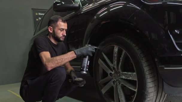 Mytí kol a gumy. Kreslení čisticího prostředku na disky v autě. Mladý muž pracuje v práci, čistí díly aut