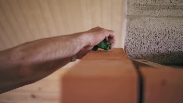 Detailní pohled na člověka tvůrce je měření cihlovou zeď s ruletou. Člověk je oprava cihlová zeď