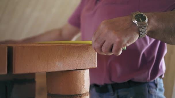 Carpenter tvůrce používá mesure ruleta k měření červený Cihlový krb. Opravář je měření krb s vodováhou