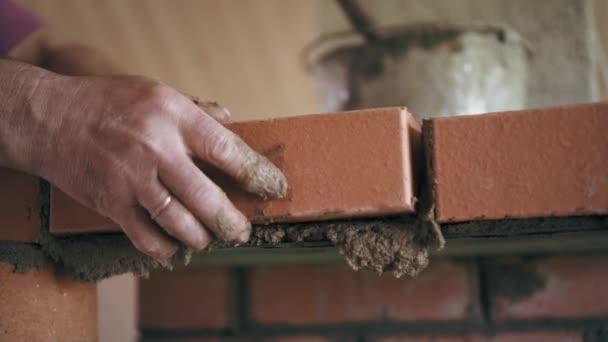 Stavební dělník je nastavení cihlu na ležel v cementárnách vybudovat krb. Detailní pohled na zděnou