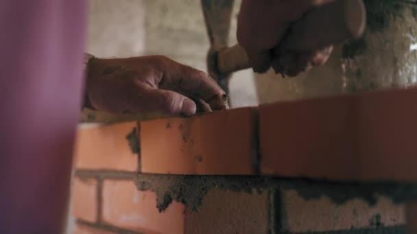 Profesionální stavební dělník staví cihlovou zeď s červenými cihlami a cemen řešení. Detailní virew na muže zarovnává úroveň cihel na webu