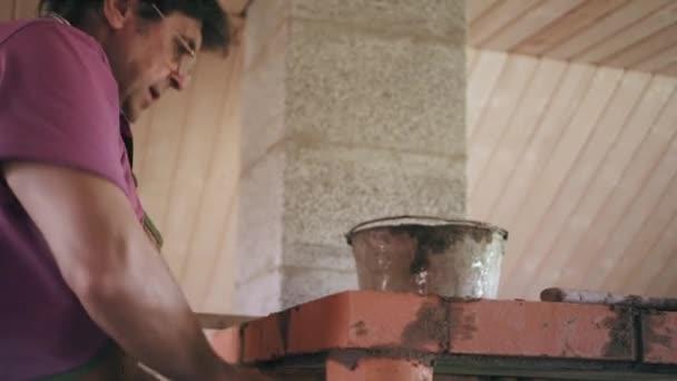 Mason je pokládání červených cihel na řešení cementu při opravě domu. Muž dává vrstvu cementu na cihlovou zeď
