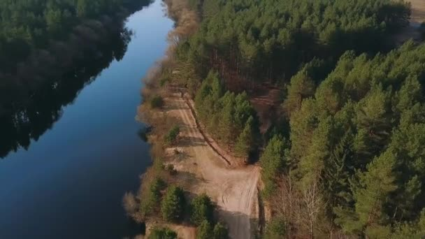 Letecké video z jarní přírody: Les a řeka. Pohled shora na malebnou krajinu