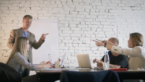 Obchodní manažer navrhuje myšlenku svým kolegům a souhlasí s ním. Kreativní podnikání jejich šéf, usmíval se a diskusi o myšlenky v úřadu týmu potleskem