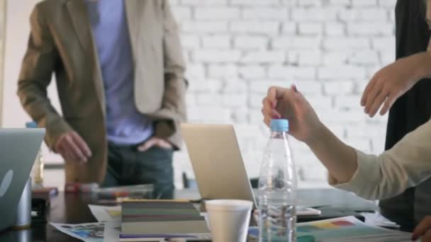 Co-workers in the office are discussing something during coffee break. Businesswoman passes a pensil to a female colleague in the business office. Friendly business partnership