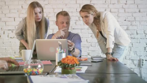 Business colleagues discussing something on laptop in the office. Coworkers partnership in common business. An employee man helps two women colleagues with project
