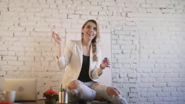 Stylový obchodních žena sedí na stole poblíž na notebooku v kreativní úřadu vyfukování bublin a usmívá se. Čelní pohled. Zpomalený pohyb