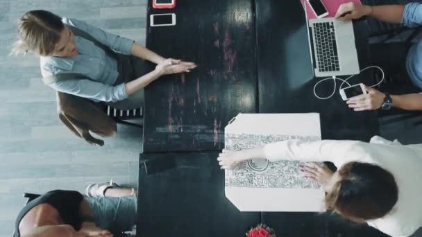 Pracovní plocha kreativní obchodního týmu, který pracuje na notebooky a komunikuje pomocí smartphonů v úřadu. Zaměstnance přináší krabici od pizzy. Coworking. Pohled shora
