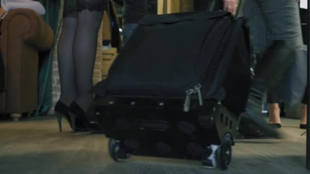 c31d34ffc6c3 Woman walk with trolley case in a crowded place indoors. Girl pull a black  wheeled suitcase and crashes into the wall. Close up view