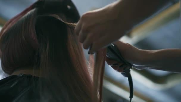 Fodrász teszi hullámos haja fogóval. Alulnézet