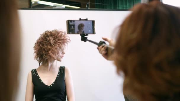 Eine Frau fotografiert auf einem Smartphone ein Modemodel mit schöner Frisur. zurück