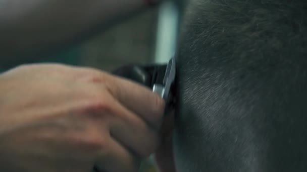 Proffesional hairdresser is cutting mans hair with electric trimmer in barber shop. Males hairstyling in hair saloon. Slow motion.