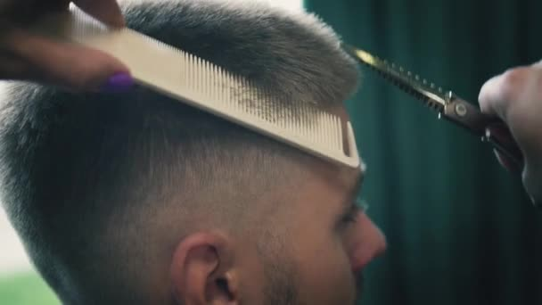 Close up view on professional haircut process in barber shop. Female hairdresser is cutting clients hair with scissors and comb in hair salon. Slow motion.