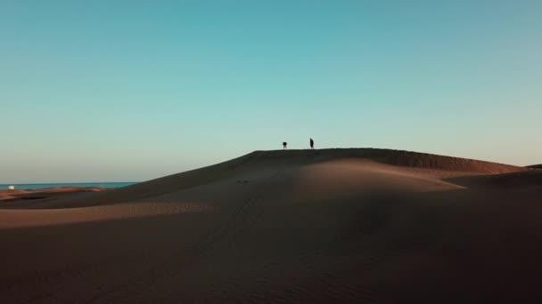 Silueta dva turisté s batohy, lezení na vrcholu písečné duny v poušti, s oceánem v pozadí. Poklidné pouštní krajina v západu slunce světlo. Gran Canaria