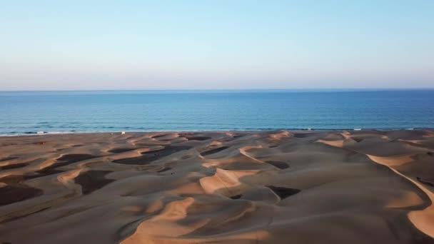 Orizzonte paesaggio del bellissimo deserto con dune di sabbia, loceano sullo sfondo e cielo blu nella luce del tramonto. Paesaggio di meravigliosa natura pacifica, aerea. Gran Canaria
