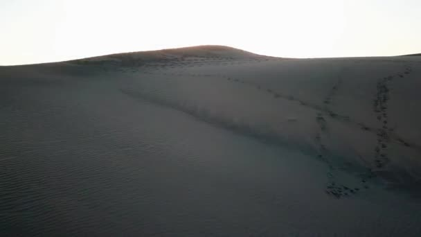 Aerial: camera flies over a desert in sunset light. Horizontal view of endless sand dunes of a desert with sun setting. Gran Canaria