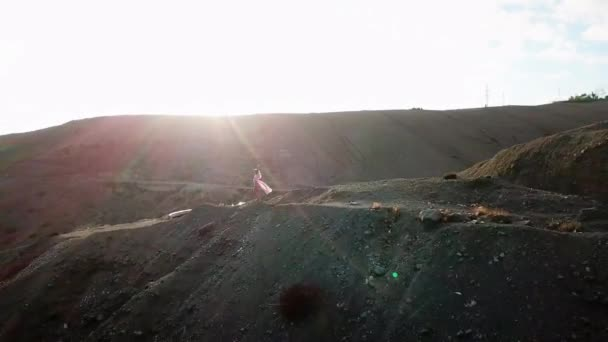 Camera flies away from beautiful female standing at a cliff near the ocean in sunset light. Summer travel to Gran Canaria.