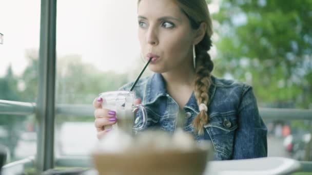 Young brunette woman drinks coffee in a coffee shop. Cafe.