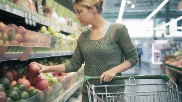 Mladá žena s vozíkem zvolí ovoce v úložišti