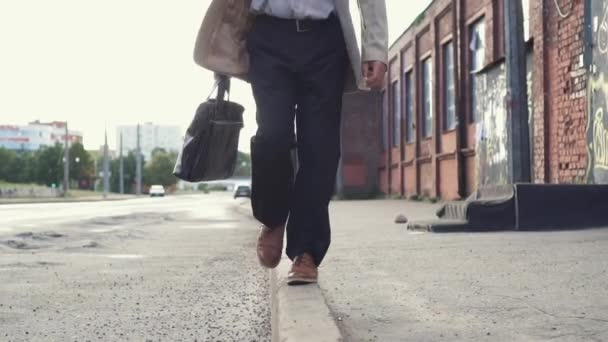 Elderly businessman in a business suit with briefcase have fun, walking on the border near the road, balancing, and smiling. Slow motion.