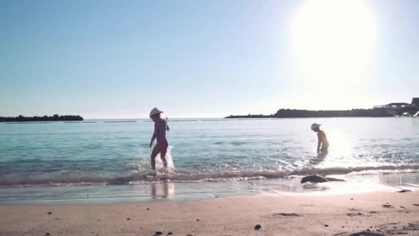 Dvě šťastné děti hrají v moři nedaleko písečné pláže. Jasný slunečný den. Dětství. Zpomalený pohyb
