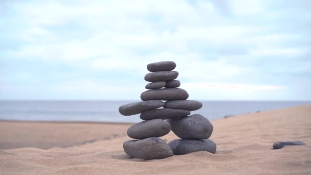 The cairn stands on the sand. The hand adds the last stone to finish the cairn. Sandy desert around