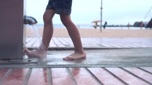 Malý chlapec v šortkách myje nohy od písku nedaleko písečné pláže v nožní sprchu. Nohy detailní zobrazení. Zpomalený pohyb