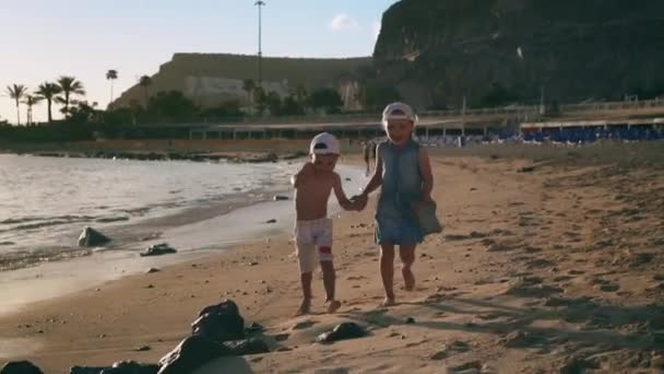 Two little happy kids hold hands and run along the beach and sea waves at sunset. Slow motion