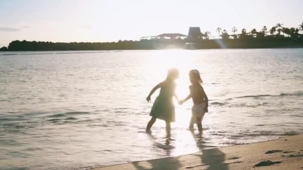Two little happy kids are standing on the beach near the sea, holding hands and kissing each other. Brother and sister. Slow motion