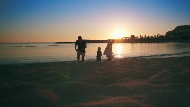 Young happy family walks along the sandy beach near the sea at sunset. Children and adults laugh and enjoy. Slow motion