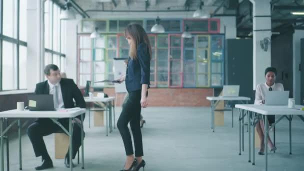 Eine Geschäftsfrau im Sakko geht ins Büro, kommuniziert mit Kollegen und gibt ihnen Aufgaben. kreativer Geschäftsbereich im Loft-Stil. Coworking. Büroleben