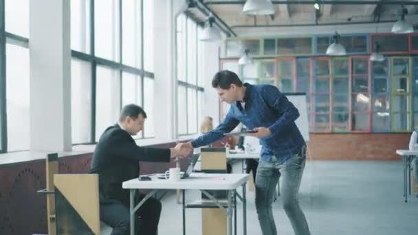 Mladý kancelářský zaměstnanec přichází do kanceláře, píše na tablet a zdraví se s kolegy. Kreativní obchodní prostor v podkrovním stylu. Spolupracuju. Kancelářský život