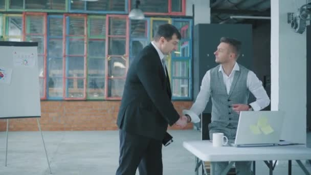 Businessman in a suit and with documents in hand walking in the office, talking and greeting with colleagues. Creative business space in loft style. Coworking. Office life