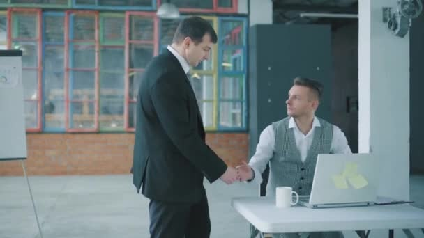 Üzletember egy öltöny és a nyakkendő dokumentumok kezében séta az irodában, kommunikál és üdvözöl kollégák. Kreatív üzleti tér Loft stílusban. Coworking. A Hivatal életciklusa