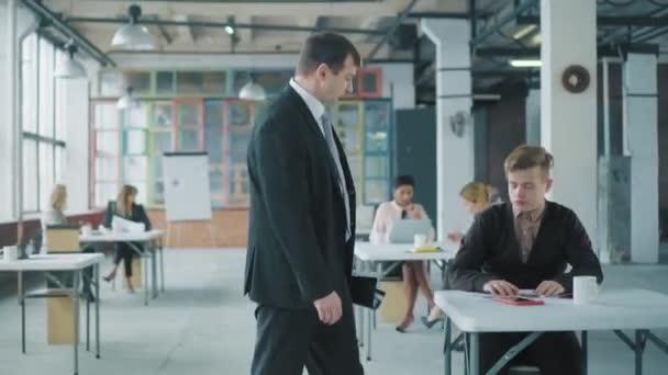 Obchodní muž v obleku a s dokumenty, které v kanceláři chodí pěšky, komunikuje s kolegy. Tvůrčí prostor ve stylu podkroví. Pracuju na tom. Život v kanceláři