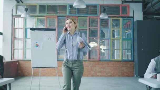 Žena, která chodí v kanceláři a mluví po telefonu, zahazuje, upustí dokumenty a dává je do pořádku. Zaměstnanci jí pomáhají. Kreativní kancelář ve stylu podkroví. Spolupracujete