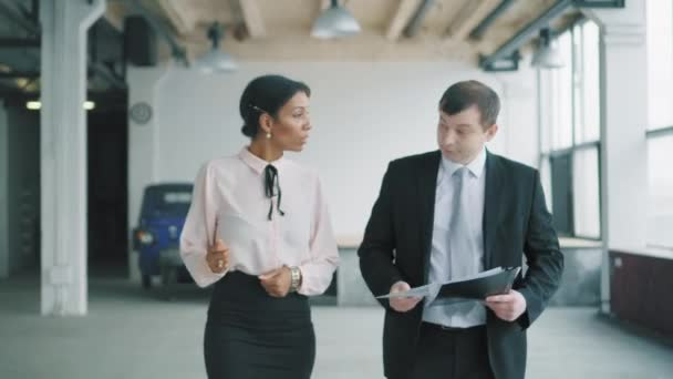 Two multi-ethnic managers, a woman and a man walk in the office and discuss the project. Creative business space in loft style. Coworking. Office life