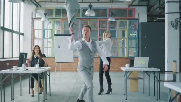 Young businessman goes to the office and starts dancing, twisting his jacket. Colleagues join and dance with him and have fun. Creative coworking in loft style. Office life