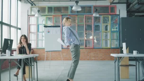 Young business woman dancing in the office, scatters documents. Colleagues join, dance with her and have fun. Creative office interior in loft style. Coworking. Office workers celebrate