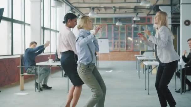 Společně tančící kolegyně. Kancelářští pracovníci slaví a tancují. Interiér kreativní kanceláře ve stylu podkroví. Spolupráce