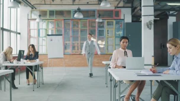 Mladý obchodník chodí po kanceláři, zaměstnankyně z africké Ameriky se s ním chce setkat na židli, vyzvedne ji a povzbuzuje ji k celé kanceláři. Život v kanceláři. Kreativní interiér