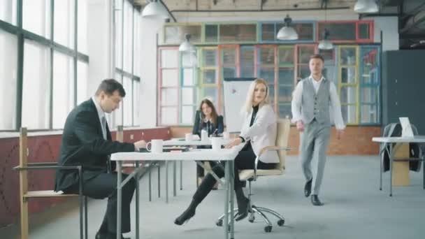 Ein junger Geschäftsmann geht durch das Büro, ein Mitarbeiter rollt ihm auf einem Stuhl entgegen, er hebt ihn auf und rollt ihn fröhlich durch das Büro. Coworking. Büroleben. Kreatives Interieur