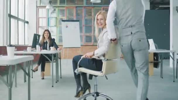 Zaměstnanci jezdí na židli kolem kanceláře. Muž se ženou. Pracuju na tom. Život v kanceláři. Kreativní interiér