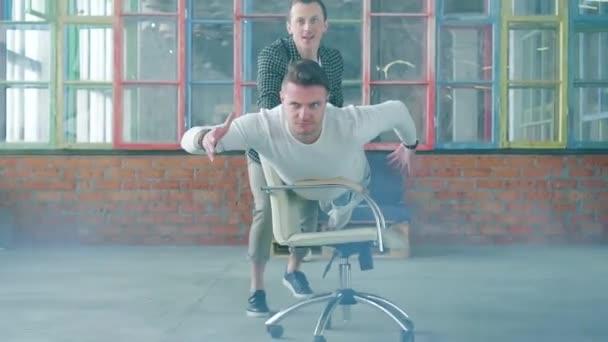 A menedzser egy szék lovaglás az irodában, mint egy Superman. Kollégája segít neki. Office-szórakozás. Füstjelző. A Hivatal életében. Üzleti csapat. Lassú Mo