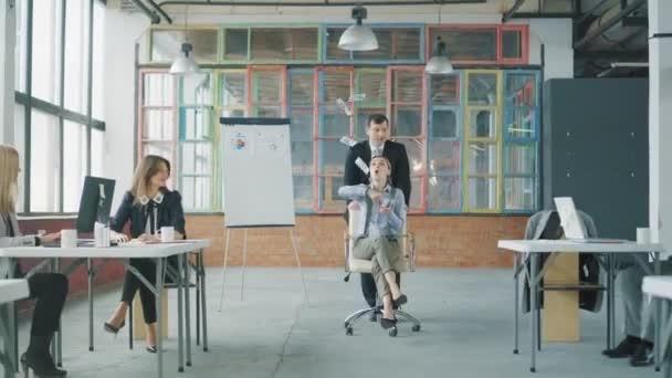 Mladá ženská manažerka jede na židli kolem kanceláře a vyhazuje peníze. Pomáhá jí kolega. Interiér tvůrčí kanceláře. Spolupracovní tým. Pracovníci systému Office