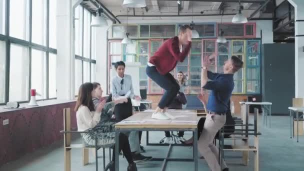 Manažeři si na stole užijí zábavu v moderní módní kanceláři a oslavují úspěch. Podnikový obchodní tým. Pracuju na tom. Zábava pro spolupracovníky
